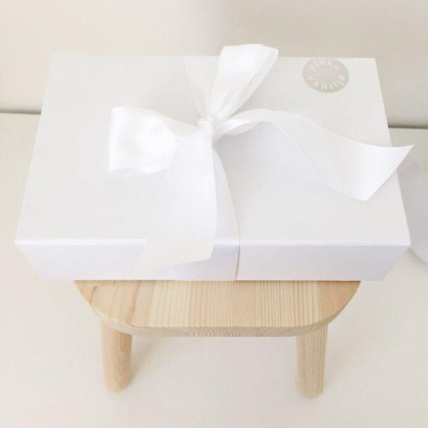 Luksuslahjapaketeissa käytämme viimeisteltyjä, magneettikiinnitteisiä valkoisia lahjalaatikoita, joita voi myöhemmin käyttää vauvamuistojen säilyttämiseen tai vauvanhuoneen sisustamiseen. Laatikot ovat mattavalkoisia ja kovakantisia. Viimesilauksen lahjalaatikot saavat leveästä valkoisesta satiininauhasta.