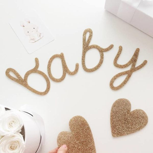 """Kaunis Baby -viiri vauvajuhliin, kultainen. Kimmeltävä glitterkultainen viiri, jossa on 2 sydäntä ja teksti """"baby"""". Kirjaimet ja sydämet on valmistettu kestävästä akryylistä, eli ne ovat napakoita ja kestäviä. Settiin kuuluu kultainen 3 metriä pitkä nauha."""