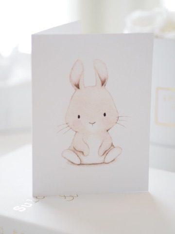 PikkuVanilja valkoinen onnittelukortti pupu. Ihana mattapintainen valkoinen kortti, jossa suloinen istuvan pupun kuva. Sisäpuolelle voit kirjoittaa tervehdyksesi. Tämä kortti on kaunis sujauttaa lahjapaketin päälle, näin se viimeistelee lahjasi tyylikkäästi.