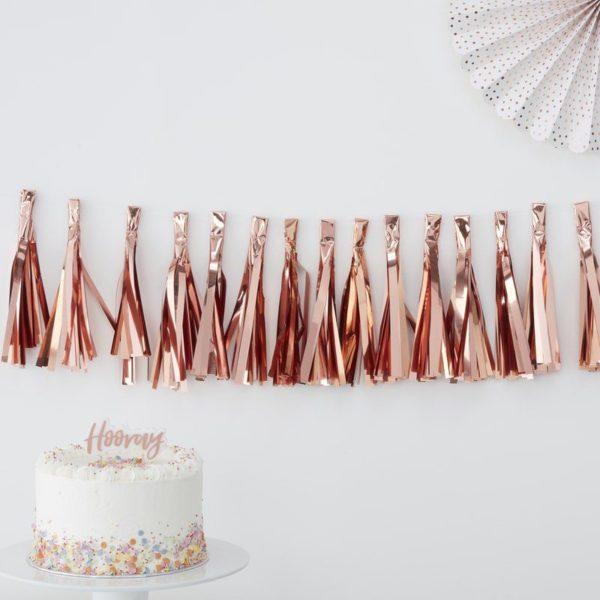 Ruusukultainen kiiltävä tasseliviiri Upeasti kiiltävä tasseliviiri luo juhlavan tunnelman juhlapäivään ja toimii kauniina taustana valokuville. Viirin nauha on läpinäkyvä ja siihen on ripustettavissa 15 tasselia, joissa on kiiltävä pinta. Juhlien lisäksi voit käyttää tasselibanneria taustana vauvan ja lasten valokuvauksessa!