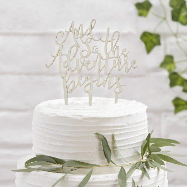 """Puinen kakun koriste Adventure Kakku ja kynttilöitä puhaltava tuikkivasilmäinen pieni -nämä hetket jäävät perhealbumiin! Kaunis kakku on juhlapöydän kruunu. Tämä yksinkertaisen tyylikäs kakun koriste on helppo, mutta näyttävä tapa luoda kaunis lasten synttärikakku! Itse kakku voi olla yksinkertainen, kun päällä on upea koriste. Lisää kakkuun vain kynttilät tai tähtisädetikku ja juhlat voivat alkaa! Puisessa kakkukoristeessa on teksti """"And so the Adventure begins"""". Teksti sopii täydellisesti minkä tahansa uuden seikkailun alkuun, joten tämä koriste on upea valinta baby showereille, ristiäisiin ja nimiäisiin! Kakulla voi juhlistaa myös lapsen eskarin- tai koulunaloitusta!"""