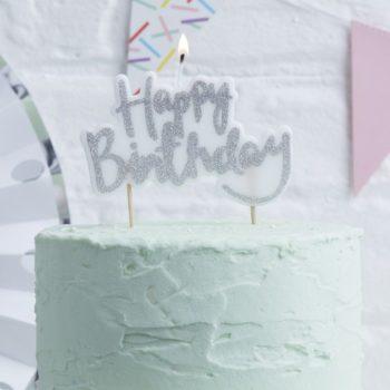 """Ginger Ray Happy Birthday kakkukynttilä hopeisella tekstillä Tämä syntymäpäiväjuhliin kauniisti sopiva kakkukynttilä näyttää upealta kakun päällä! Valkoisessa kynttilässä on """"Happy Birthday"""" -teksti hopeisella värillä."""