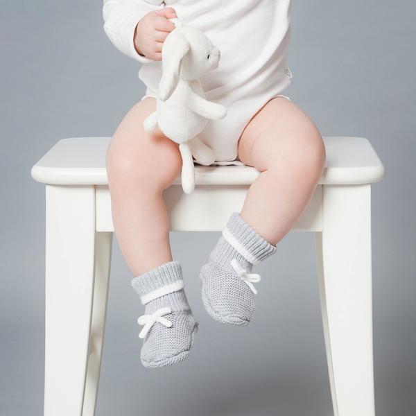 Baby Mori vauvan tossut, Knitted Grey Vaaleanharmaat valkoisilla yksityiskohdilla viimeistellyt tossut pitävät pienet varpaat lämpöisenä! Harmaiden tossujen varsi on kapeampi, jotta tossut pysyvät hyvin jalassa, mutta tarpeeksi joustava, jotta tossut saa helposti vauvan jalkaan.