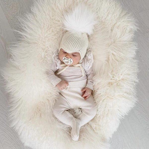 Sohvila Design Nooa vauvanpipo natural -tupsulla Käsinneulottu merinovillainen vauvan myssy perheen pienimmille. Pipossa on neulotut pehmeät nyörit, jotka pitävät myssyn paikallaan. Lämpöinen pipo on muodoltaan sellainen, että se istuu päässä tyylikkäästi ja suojaa pienen kasvoja todella hyvin.