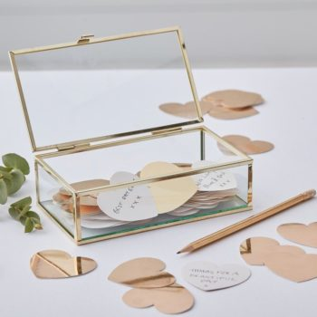 Ginger Ray Elegant Gold Glass Box with Hearts Voit käyttää tätä boksia monella tavallla: se toimii vaihtoehtoisena vieraskirjana babyshowereilla, ristiäisissä ja lapsen synttäreillä. Jokainen vieras voi kirjoittaa päivänsankarille oman tervehdyksensä tai toivomuksensa kiiltäville sydänkorteille, jotka säilyvät kauniisti kultaisilla yksityiskohdilla viimeistellyssä lasiboxissa. Tyylikäs laatikko on myös kaunis lahja ystävälle, äidille tai omalle puolisolle! Kirjoita kortteihin asioita, joista lahjansaajassa pidät, lisää sekaan rohkaisevia lauseita -näin korteille tallentuu pieniä, yksinkertaisia asioita, joita ei kuitenkaan arjessa tule sanottua ääneen. Näin ikimuistoinen lahjasi on valmis!
