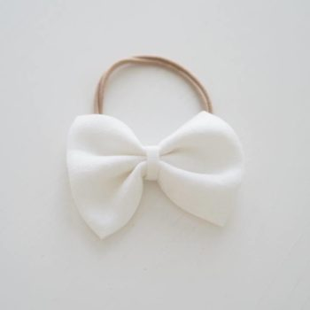 Sievä käsintehty rusettipanta vauvalle Nora, valkoinen. Pehmeä ja todella hyvin joustava panta on viimeistelty klassisen kauniilla Alma pellavarusetilla.Sievän rusettien tyylion kaunista, romanttista, tyttömäistä ja yksinkertaista. Rusettien tarkoitus ei ole viedä huomiota niiden käyttäjältävaan korostaa tytön omia ihania piirteitä! Rusettipanta sopii käytettäväksi vastasyntyneestä lähtien.