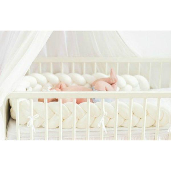 Wood'n'Wool palmikkopehmuste vauvansänkyyn, valkoinen. Tyylikäs pehmuste suojaa vauvaa kolhimasta itseään pinnasängyn laitoja vasten. Palmikkopehmuste on napakka, joten se asettuu hyvin paikoilleen. Pienet valkoiset kiinnitysnauhat auttavat pitämään pehmusteen oikeassa asennossa.Palmikkopehmuste viimeistelee pinnasängyn sisustuksen kauniisti ja on upea yksityiskohta lastenhuoneessa!