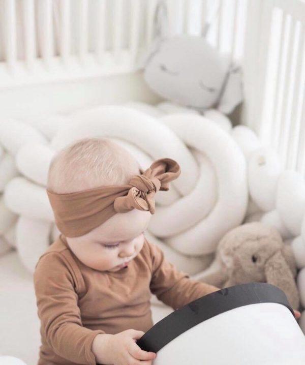 Wood'n'Wool korkea reunapehmuste vauvansänkyyn, valkoinen Tyylikäs pehmuste suojaa vauvaa kolhimasta itseään pinnasängyn laitoja vasten. Palmikkopehmuste on napakka, joten se asettuu hyvin paikoilleen. Pienet valkoiset kiinnitysnauhat auttavat pitämään pehmusteen oikeassa asennossa. Tämä Wood'n'Woolin korkeampi malli antaa vauvalle enemmän suojaa ja omaa rauhaa.
