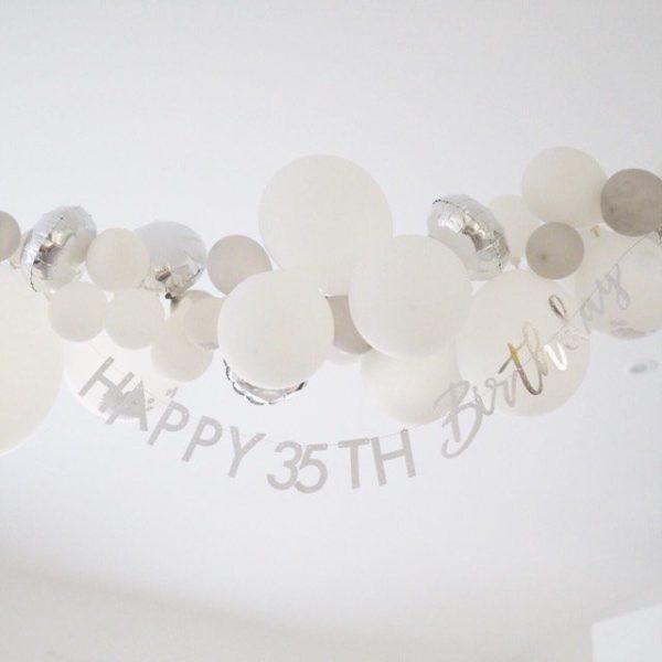 """Ginger Ray muunneltava kimmeltävä Happy Birthday -viirinauha, iridescent hopea Ohueen nauhaan saat pujotettua hopeisilla kiiltävillä kirjaimilla tekstin """"Happy Birthday"""" ja synttärisankarin iän. Tämä tyylikäs banneri luo juhliin viimeisteltyä tunnelmaa ja voit yhdistää sen kauniisti ilmapalloihin, pom pom -koristeisiin tai foliopalloihin!"""