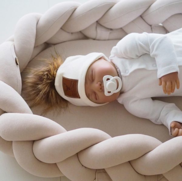 Kaunis palmikkoreunainen unipesä toimii pehmeänä alustana ja rauhoittavana nukkumapaikkana vauvalle. Voit laittaa unipesän ensin pinnasänkyyn ja luoda vastasyntyneelle pesämäisemmän nukkumapaikan, sillä sellaisenaan pinnasänky on aluksi valtavan kokoinen pienelle vauvalle. Moni pitää unipesää vanhempien sängyssä keskellä, jotta vauva on öisin lähellä, mutta kuitenkin vähän omassa rauhassaan. Tätä unipesää voit myös käyttää vaipanvaihtoalustana vaipanvaihtopisteellä.