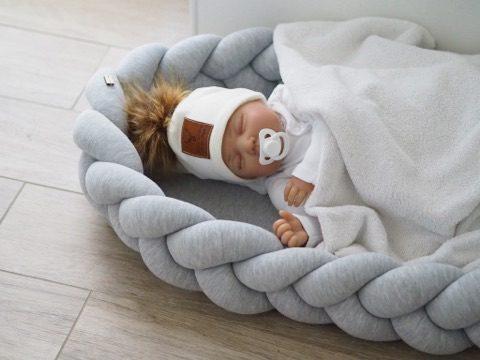 Wood'n'Wool vaaleanharmaa unipesä vauvalle. Kaunis palmikkoreunainen unipesä toimii pehmeänä alustana ja rauhoittavana nukkumapaikkana vauvalle. Voit laittaa unipesän ensin pinnasänkyyn ja luoda vastasyntyneelle pesämäisemmän nukkumapaikan, sillä sellaisenaan pinnasänky on aluksi valtavan kokoinen pienelle vauvalle. Moni pitää unipesää vanhempien sängyssä keskellä, jotta vauva on öisin lähellä, mutta kuitenkin omassa rauhassaan. Kun unipesää ei enää tarvita, irrotettavasta palmikkoreunasta saat kauniin reunapehmusteen vauvan pinnasänkyyn!