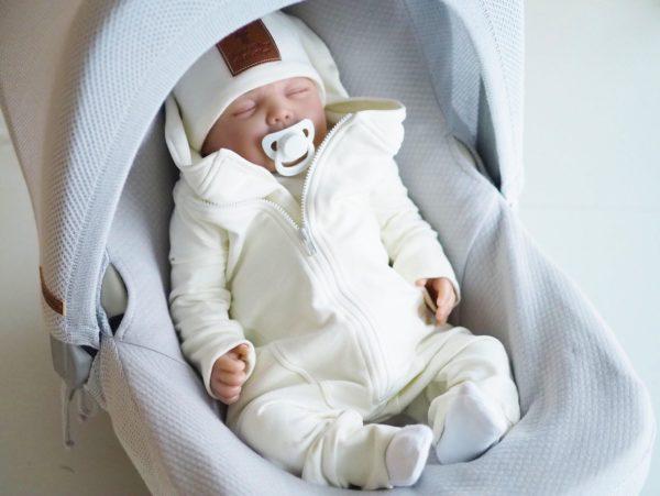 Gugguu Baby Jumpsuit on hyvin laadukas vauvanhaalari suojaavalla hupulla. Tyylikäs, paksummasta kankaasta ommeltu haalari sopii hyvin päivittäiseen käyttöön ja on tosi tykätty vaate käytettäväksi yhdessä lämpöpussin ja tupsupipon kanssa turvakaukalossa. Haalari on todella mukava vaate vauvalle: mikään ei paina tai kiristä vatsaa. Vauvaa on myös helppo nostaa syliin haalarissa, selkä pysyy piilossa ja lämpimässä. Pearl White -sävyisessä haalarissa on valkoinen vetoketju.