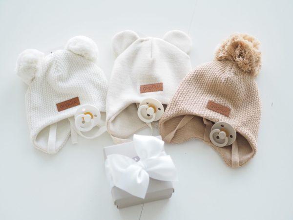 Gugguu Baby Beanie luksussetti Natural tones Tässä kauniisti pakatussa lahjapaketissa on 3 vauvanpipoa ja niiden kanssa yhteensopivat BIBS tutit. Ajattomat sävyt sopivat yhteen monen vaatteen ja asusteen kanssa! Yksinkertaisen tyylikkäät nauhapipot on ommeltu pehmeästä ja joustavasta kankaasta. Luomupuuvillaiset pipot tuntuvat mukavalta lapsen päässä eivätkä hankaa. Hyvin istuvat pipot pysyvät paikallaan valumatta silmille. Tämä pipomalli suojaa korvien lisäksi tehokkaasti myös vauvan poskia!